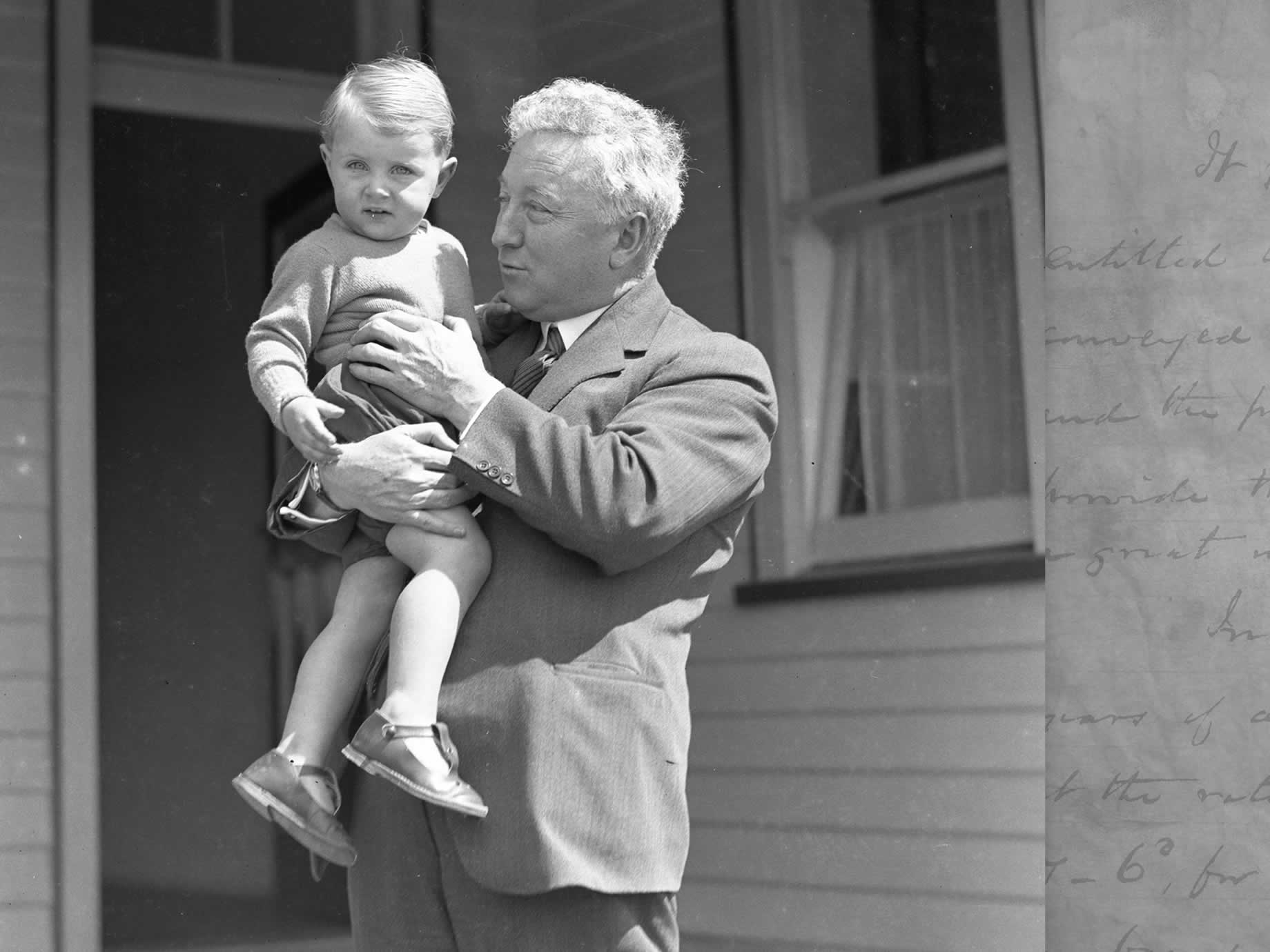 Joe Lyons outside the back door of his home with a young child in the mid 1920s